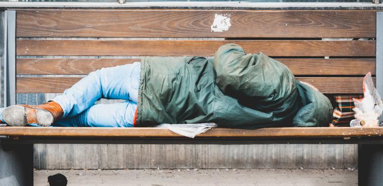 Bezdomny śpiący na ławce