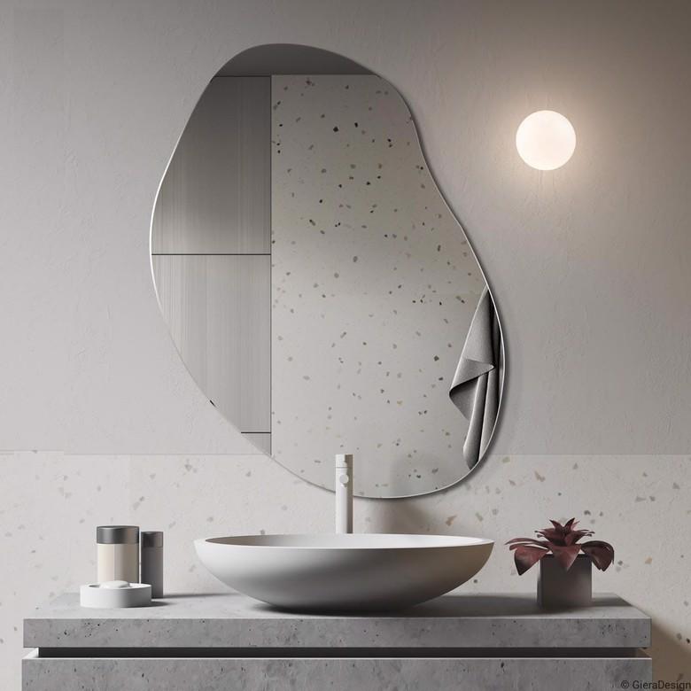 Lustro o nieregularnym kształcie nad umywalką, biała łazienka