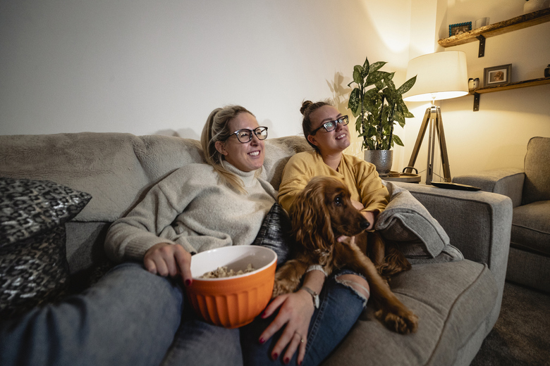 Para kobiet z psem na kanapie, popcorn